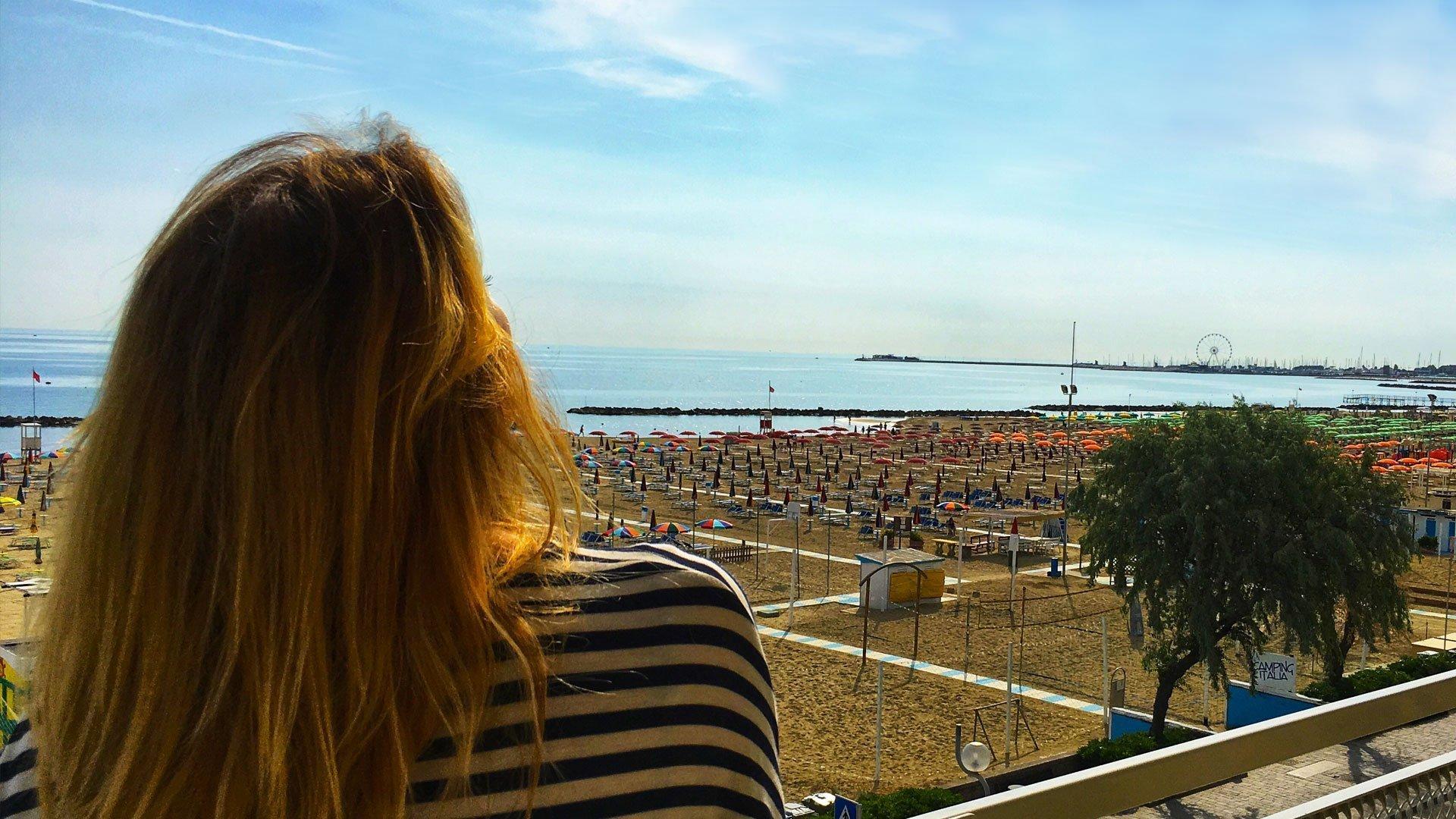 ragazza che guarda la vista mare dal balcone Hotel Tritone lungomare di Viserba di Rimini