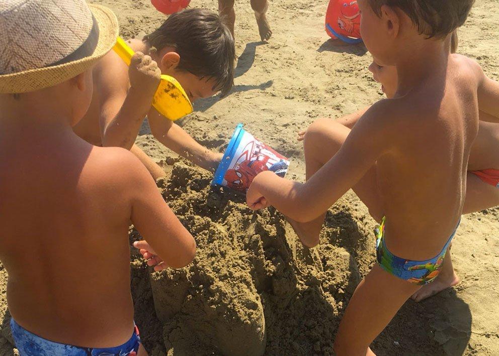 bambini in spiaggia a Viserba di Rimini che distruggono i castelli di sabbia