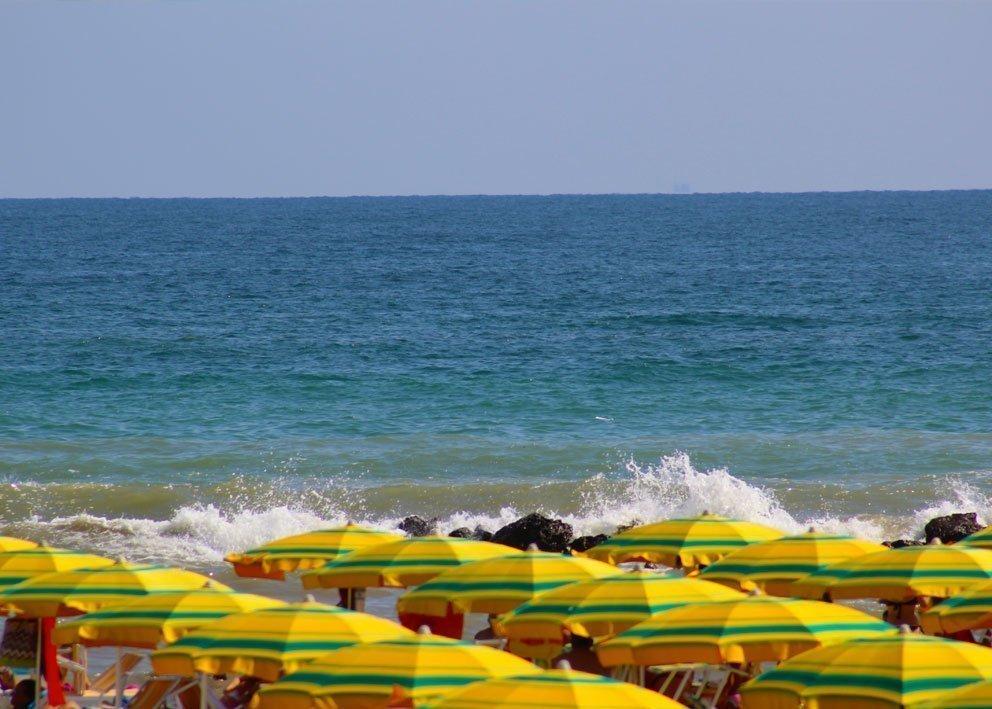 vista mare dall'Hotel Tritone fronte mare Rimini. ombrelloni gialli mare blu e onde sugli scogli