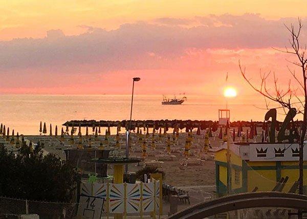 vista del tramonto dall' hotel tritone di Rimini. Sole arancione e barca in mezzo al mare